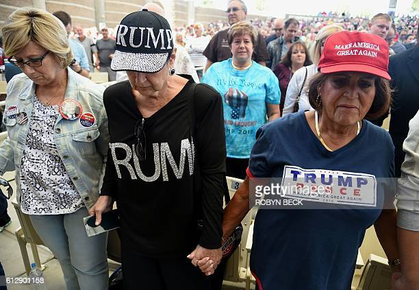 Supporters of Republican presidential candidate Donald Trump pray at the start of a Trump campaign rally at the Henderson Pavilion, October 5, 2016...