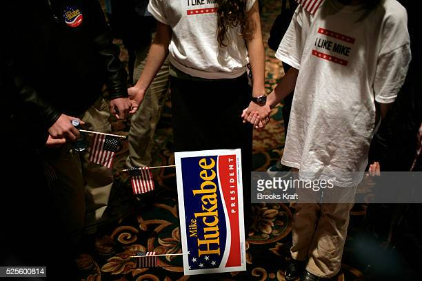 Supporters of Republican presidential candidate Mike Huckabee pray before his Iowa Caucus celebration in Des Moines.