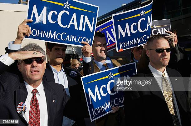 Supporters of Republican US presidential hopeful and US Sen John McCain hold posters as he visits a polling station at Mahaffey Theater January 29...