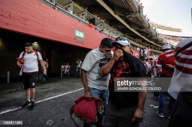 TOPSHOT Supporters of River Plate cover their faces after being affected by pepper gas sprayed by police outside the Monumental stadium in Buenos...