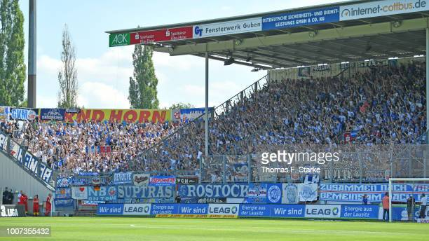 Supporters of Rostock cheer their team during the 3. Liga match between FC Energie Cottbus and F.C. Hansa Rostock at Stadion der Freundschaft on July...