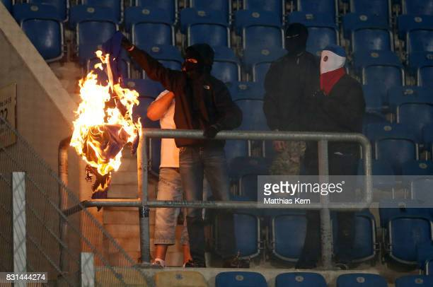 Supporters of Rostock set merchandise articles of Berlin on fire during the DFB Cup first round match between FC Hansa Rostock and Hertha BSC at...