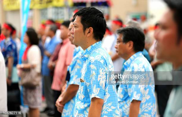 Supporters of ruling Liberal Democratic Party backed candidate Atsushi Sakima listen his street speech as the Okinawa gubernatorial election...