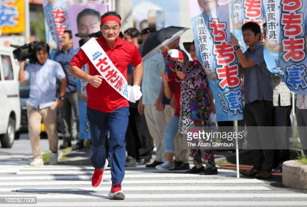 Supporters of ruling Liberal Democratic Party backed candidate Atsushi Sakima runs to cross a road as the Okinawa gubernatorial election officially...