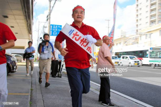 Supporters of ruling Liberal Democratic Party backed candidate Atsushi Sakima runs as the Okinawa gubernatorial election officially kicks off on...