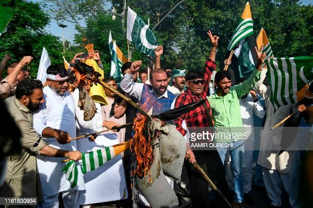 Supporters of ruling Pakistan Tehreek-e-Insaf burn an effigy of Indian Prime Minister Narendra Modi as they march toward the Indian High Commission...