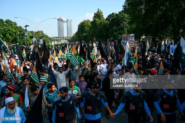 Supporters of ruling Pakistan TehreekeInsaf march toward the Indian High Commission during a protest rally in Islamabad on August 15 as the country...