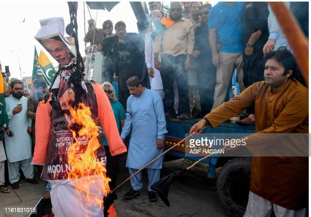 Supporters of ruling Pakistan Tehreek-e-Insaf party burn an effigy of Indian Prime Minister Narendra Modi during a protest in Karachi on August 15 as...