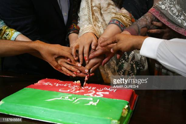 """Supporters of ruling Pakistan Tehreek-e-Insaf party of Imran Khan, cut a cake in Islamabad on July 25 to celebrate and observe """"Thanks Giving Day""""..."""