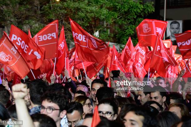 Supporters of ruling Spanish Socialist Party wave flags as they celebrate in front of the party headquarters in Madrid after Spain held general...