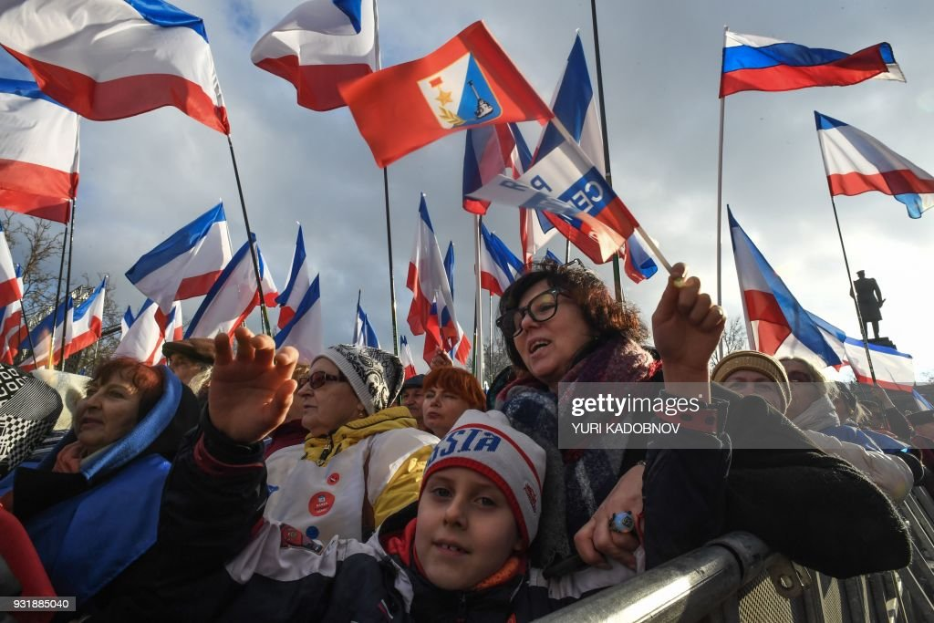 TOPSHOT - Supporters of Russian President Vladimir Putin gather for a rally to celebrate the fourth anniversary of Russia's annexation of Crimea at Sevastopol's Nakhimov Square on March 14, 2018. Russia will vote for President on March 18, 2018. / AFP PHOTO / Yuri KADOBNOV