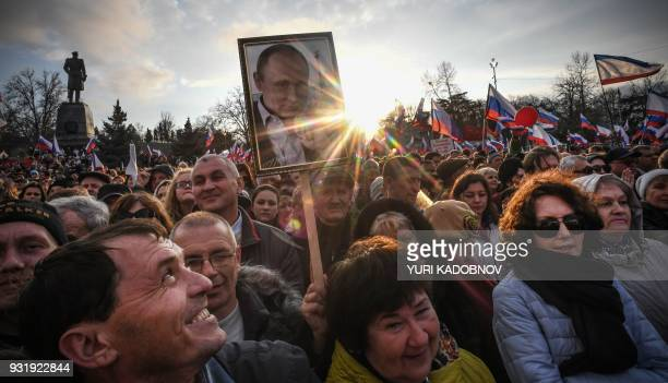Supporters of Russian President Vladimir Putin gather for a rally to celebrate the fourth anniversary of Russia's annexation of Crimea at...