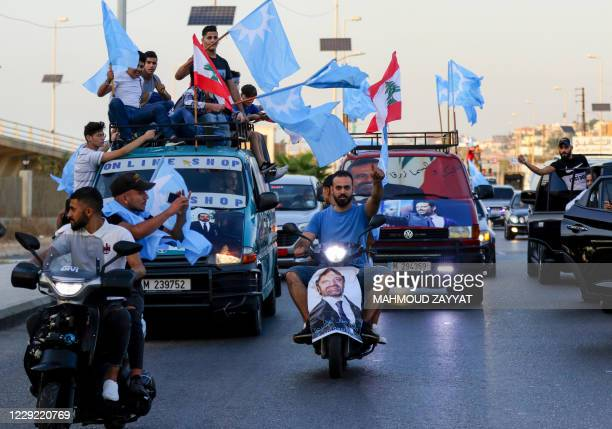 Supporters of Saad Hariri's Future Movement Party wave the party flag and the national flag during a parade to celebrate him being tasked with...