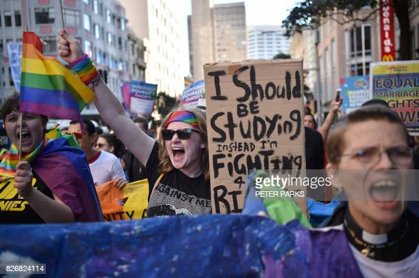 Supporters of same sex marriage carry banners and shout slogans as they march in Sydney on August 6 2017 Australia's Liberal Party the senior partner...