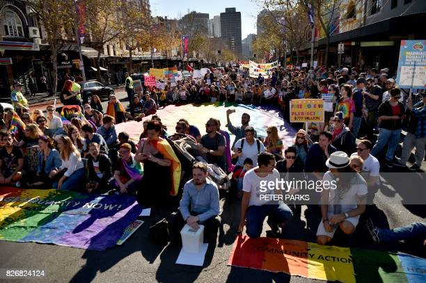 Supporters of same sex marriage carry banners and shout slogans as they gather on a street in Sydney on August 6 2017 Australia's Liberal Party the...
