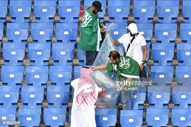 Supporters of Saudi Arabia clean the stands at the end of the Russia 2018 World Cup Group A football match between Uruguay and Saudi Arabia at the...