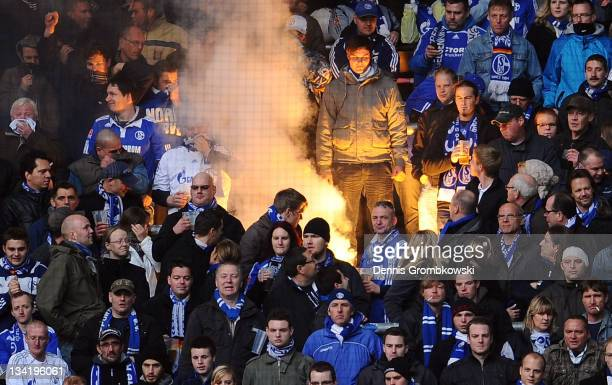 Supporters of Schalke ignite fireworks while Clemens Toennies chairman of Schalke looks on during the Bundesliga match between Borussia Dortmund and...