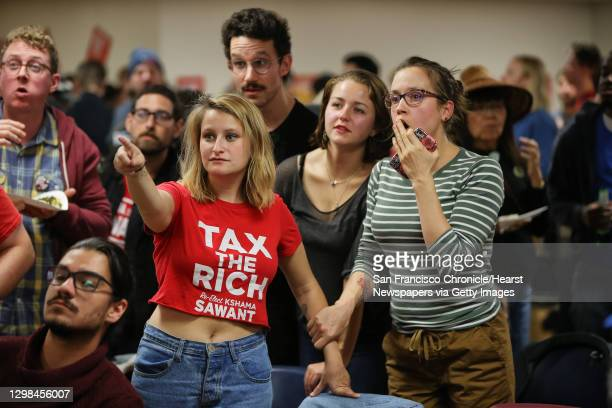 Supporters of Seattle City Council District 3 incumbent candidate Kshama Sawant react as the 8pm election night numbers drop is revealed, putting...
