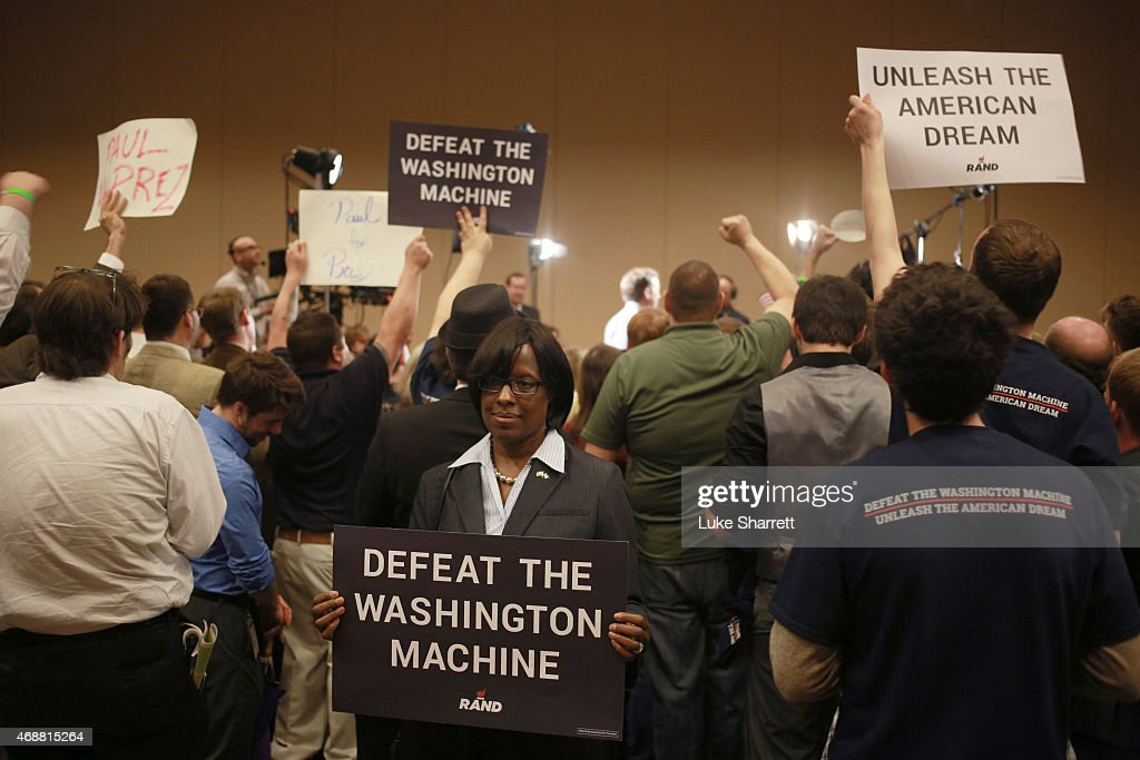 Supporters of Sen. Rand Paul (R-KY) hold signs as he is interviewed by Fox News after announcing his candidacy for the 2016 Republican presidential nomination during an event at the Galt House Hotel on April 7, 2015 in Louisville, Kentucky. Originally an ophthalmologist, Paul rode the Tea Party wave to office in 2010.