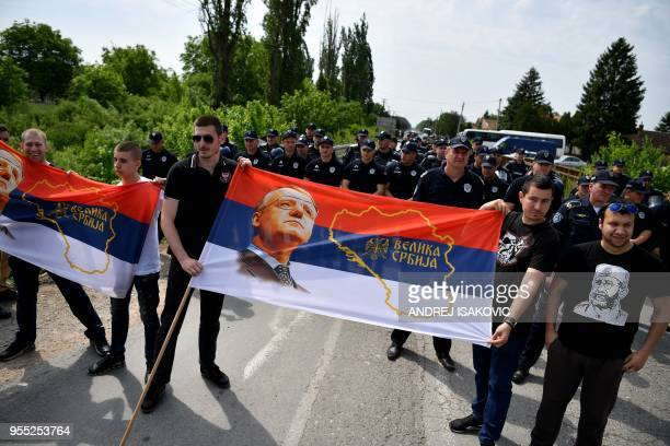 Supporters of Serbian Radical Party leader Vojislav Seselj holding a flag depicting the map of 'Great Serbia' stand in front of a police cordon that...