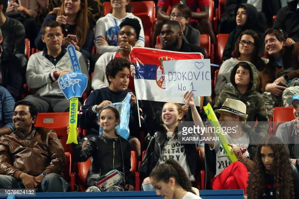 Supporters of Serbia's Novak Djokovic cheer for him with a Serbian flag during his ATP Qatar Open quarterfinal match against Nikoloz Basilashvili of...