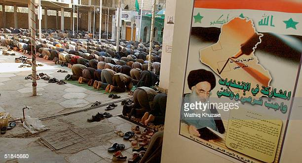 Supporters of Shiite cleric Ayatollah al-Sistani pray at a Friday prayer service as a poster urging for participating in the coming elections is seen...
