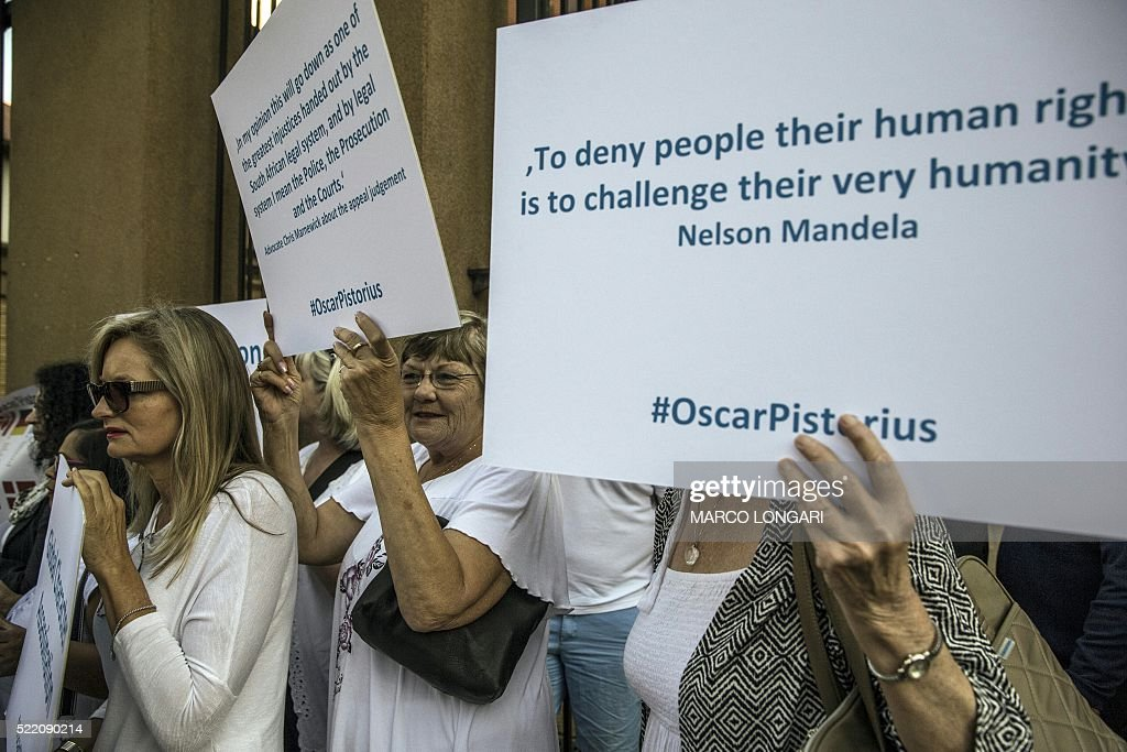 Supporters of South African Paralympian Oscar Pistorius hold placards outside the High Court in Pretoria ahead of today's postponement hearing on April 18, 2016. / AFP / MARCO