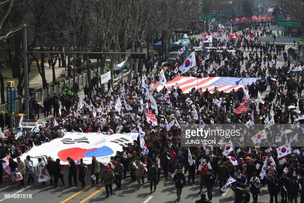 Supporters of South Korea's impeached expresident Park GeunHye carry huge flags of South Korea and the US as they march toward the Constitutional...