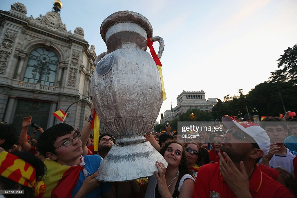 Supporters of Spain's national football team hold a home-made replica trophy aloft to congratulate their team's players as they return to Madrid following their victory in the UEFA EURO 2012 football championships on July 2, 2012 in Madrid, Spain. Spain beat Italy 4-0 in the UEFA EURO 2012 final match in Kiev, Ukraine, on July 1, 2012.