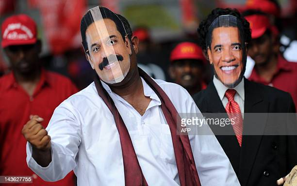 Supporters of Sri Lanka's Marxist JVP party wear masks featuring Sri Lankan president Mahinda Rajapaksa and US president Barack Obama during the...