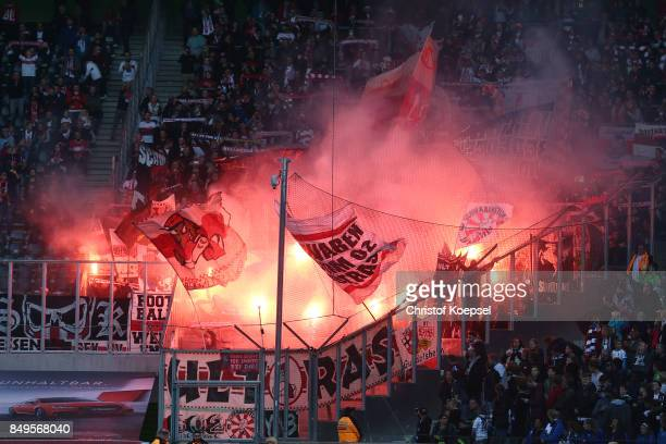 Supporters of Stuttgart light flares and wave their flags before the Bundesliga match between Borussia Moenchengladbach and VfB Stuttgart at...