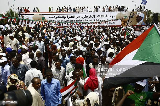 Supporters of Sudanese President hold national flags and deploy a banner during a ceremony in his honour upon his return in the country from Ethiopia...