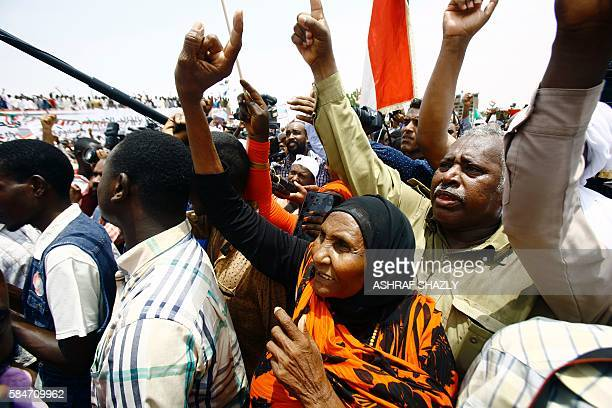 Supporters of Sudanese President shout slogans during a ceremony in his honour upon his return in the country from Ethiopia on July 30 2016 in the...
