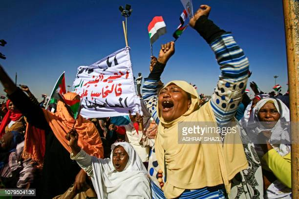 TOPSHOT Supporters of Sudan's President Omar alBashir shout slogans as they gather during a rally for him in the Green Square in the capital Khartoum...