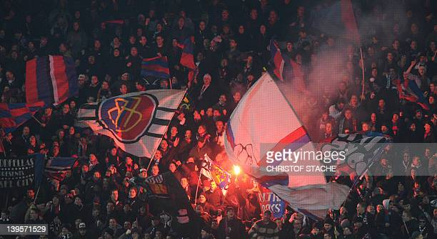 Supporters of Swiss football team FC Basel celebrate during the UEFA Champions League round of sixteen first leg match between Bayern Munich and FC...