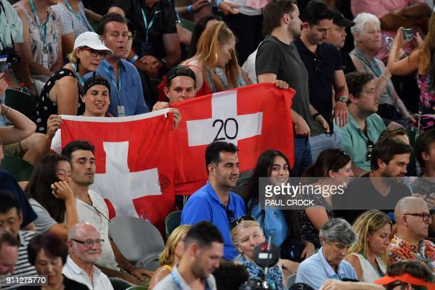 Supporters of Switzerland's Roger Federer wave a national flag during his men's singles final against Croatia's Marin Cilic on day 14 of the...