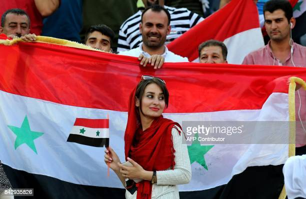 Supporters of Syria cheer for their team during the FIFA World Cup 2018 qualification football match between Iran and Syria at the Azadi Stadium in...