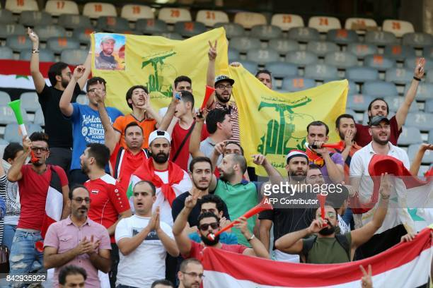 Supporters of Syria some of them holding flags of Shiite movement Hezbollah cheer for their team during the FIFA World Cup 2018 qualification...
