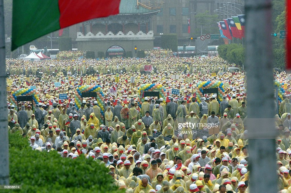 Supporters of Taiwan President Chen Shui-bian in raincoats, join the inauguruation ceremony in front of Presidential Palace in Taipei 20 May 2004. President Chen Shui-bian refused to rule out eventual reunification with China, after Beijing threatened to crush any moves by the island towards independence. AFP PHOTO/Sam YEH