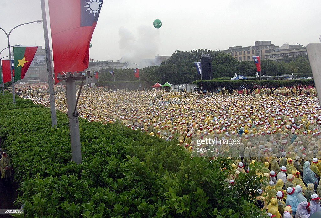 Supporters of Taiwanese President Chen Shui-bian wearing raincoats, join the inauguration ceremony in front of Presidential Palace in Taipei 20 May 2004. Taiwan's President Chen Shui-bian refused to rule out eventual reunification with China, after Beijing threatened to crush any moves by the island towards independence. AFP PHOTO/Sam YEH
