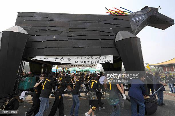 Supporters of Taiwan's presidential candidate Frank Hsieh of the ruling Democratic Progressive Party push a black wooden horse to mock the opposition...