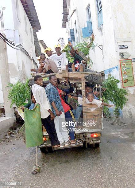 Supporters of Tanzania's ruling Chama cha Mapinduzi celebrate in the streets of Zanzibar 07 November 2000 after hearing that CCM's candidate Amani...