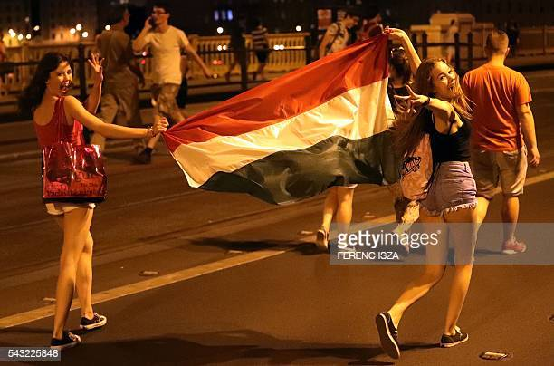 Supporters of team Hungary carry their national flag on June 26 2016 in Budapest during the Euro 2016 football match against Belgium being played in...