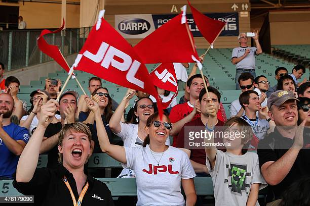 Supporters of Team RoboSimian from Jet Propulsion Labs wave handmade pennants during the Defense Advanced Research Projects Agency Robotics Challenge...