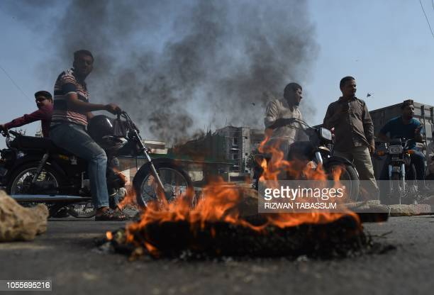 TOPSHOT Supporters of TehreekeLabaik Pakistan a hardline religious political party block the road during a protest against the court decision to...