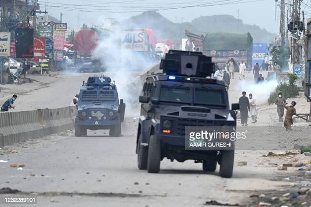 Supporters of Tehreek-e-Labbaik Pakistan party throw stones over the police armoured vehicle during a protest against the arrest of their leader as...