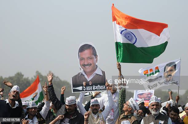 Supporters of the Aam Aadmi Party watch as leader Arvind Kejriwal is sworn in as Delhi chief minister by Delhi Lieutenant Governor Najeeb Jung during...