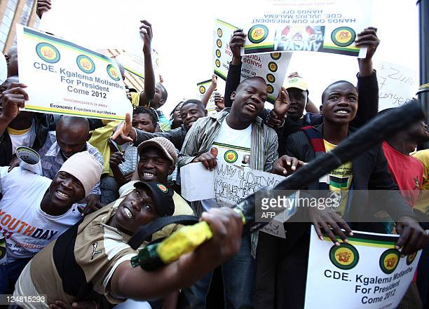 Supporters of the African National Congress youth leader Julius Malema sing and raise placards on September 2 2011 outside the ANC Luthuli house in...