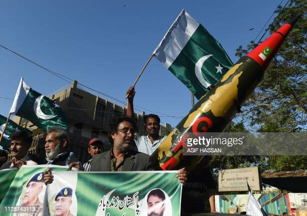 Supporters of the All Pakistan Muslim League Quid hold national flags beside a replica of a missile during an antiIndia protest in Karachi on March 5...
