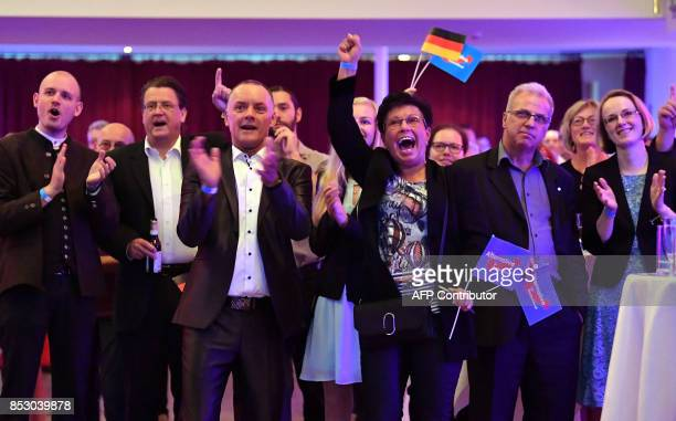 Supporters of the Alternative for Germany react after exit poll results were broadcasted on public television at an election night event in Erfurt...